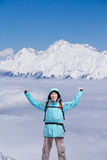 Happy male mountaineer man with raised arms. In background high mountains above clouds . Royalty Free Stock Image