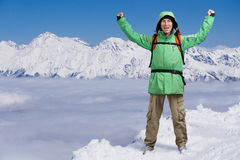 Happy male mountaineer man with raised arms. In background high mountains above clouds . Stock Images