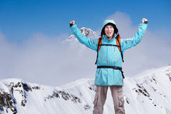 Happy male mountaineer man with raised arms. In background high mountains above clouds . Royalty Free Stock Photos