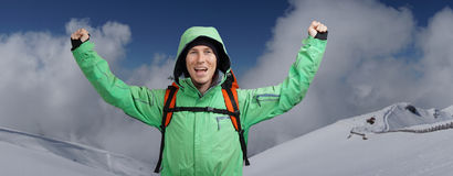 Happy male mountaineer man with raised arms. In background high mountains above clouds . Stock Photos
