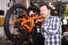 Happy male mounts bicycle parts for assembly bike in shop Stock Photography