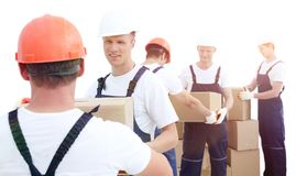 Group of people builders with boxes. Happy male movers in uniform carrying boxes Royalty Free Stock Photo
