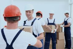 Group of people builders with boxes. Happy male movers in uniform carrying boxes Royalty Free Stock Photos
