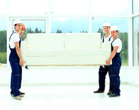 Happy male movers in uniform carrying Stock Photo