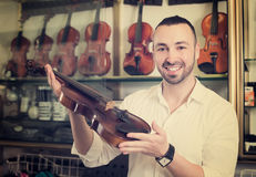 Happy male musician selecting classical violin Stock Photo