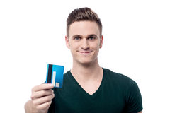 Happy male offering his credit card. Young man showing debit card to camera Royalty Free Stock Photo