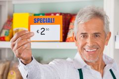 Happy Male Owner Showing Discount Sign In Store. Portrait of happy senior male owner showing discount sign in grocery store stock photos