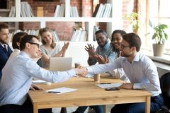 Happy partners shake hands get team applause after successful negotiations royalty free stock images