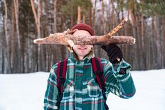 Happy male person hiking in winter forest. Smiling man in checkered winter shirt holds a log of pine wood royalty free stock photography