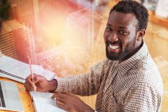 Happy male person looking at camera. Here I am. Delighted dark-skinned man keeping smile on his face and turning head while sitting at his workplace Stock Photo