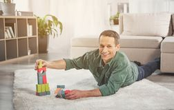 Happy male person playing with toy on carpet royalty free stock image