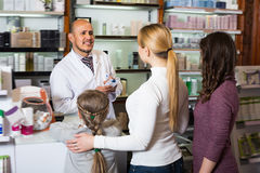 Happy male pharmacist helping customers. Happy male pharmacist wearing white coat standing next to shelves with medicine and helping customers Stock Photos