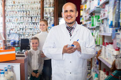 Happy male pharmacist standing next to shelves Royalty Free Stock Photo