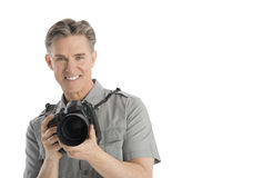 Happy Male Photographer With Camera And Umbrella Lights. Portrait of happy mature male photographer with camera and umbrella lights isolated over white Stock Images