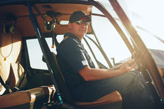 Happy male pilot in a helicopter cockpit Stock Photos