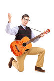 A happy male playing a guitar and singing Royalty Free Stock Image