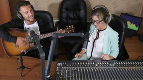 Happy male playing on stringed musical instrument next to radio presenter near equipment in radio show. Happy male in earphones playing on stringed musical stock video