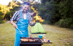 Happy male preparing bbq meat. Happy male grilling bbq meat outdoor in nature stock image