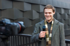 A happy male reporter leads a report on the camera on the street. A happy male reporter leads a report on the camera on the street Stock Photo
