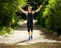 Happy Male Runner. Young athlete celebrating and raising his fists in triumph Royalty Free Stock Images