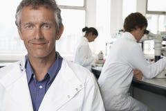 Happy Male Scientist In Laboratory. Portrait of happy male scientist with colleagues working in background Stock Image