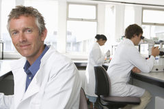 Happy Male Scientist In Laboratory. Portrait of happy male scientist with colleagues working in background Stock Images