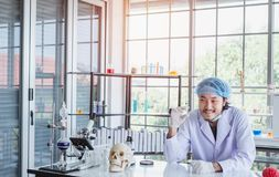 A happy male scientist showing the successful results of his experiment in a science lab. Where there are chemical substances and equipment. Scientist concept stock photo