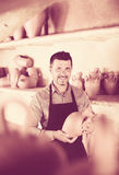 Happy male sculptor having ceramics in hands. And standing in workroom stock photography
