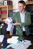 Happy male seller displaying diverse cloths. In clothes shop Stock Images