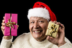 Happy Male Senior Showing Two Wrapped Presents. Convivial elderly gentleman showcasing a wrapped present in each hand, one gold, one pink. Red Santa Claus cap Royalty Free Stock Photography