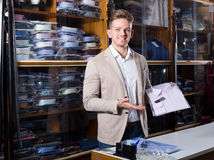 Happy male shopping assistant offering shirts. Happy male shopping assistant offering various shirts in men's cloths store Royalty Free Stock Photography