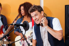 Happy Male Singer Wearing Headphones While Performing With Band. Portrait of happy male singer wearing headphones while performing with band in recording studio Royalty Free Stock Photo