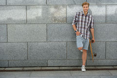 Happy male skateboarder relaxing outdoors Royalty Free Stock Image