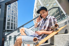 Happy male skateboarder talking on smartphone. Joyful young man is using phone for communication. He is looking at camera and smiling. Guy is sitting on steps Royalty Free Stock Images