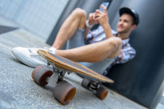 Happy male skater entertaining with smartphone. Cheerful young man is using mobile phone and smiling. He is sitting and leaning on column. Focus on skateboard Royalty Free Stock Photography