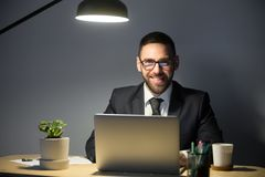Happy male smiling to camera while working in office. Happy CEO smiling at camera while working at laptop late at night under lamp light, sitting and posing at Royalty Free Stock Image