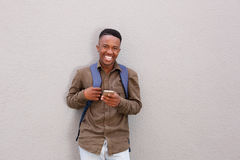 Happy male student with bag holding mobile phone. Portrait of happy male student with bag holding mobile phone Stock Photos