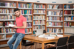 Happy Male Student With Book In Library. In The Library - Handsome Arabic Male Student With Laptop And Books Working In A High School - University Library Royalty Free Stock Image