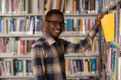 Happy Male Student With Book In Library Stock Photos