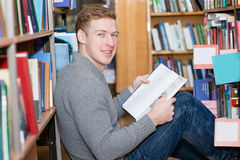 Happy male student with book sitting on floor in library.  Stock Photo