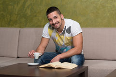 Happy Male Student In Cafe With Book Royalty Free Stock Image