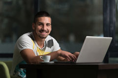 Happy Male Student In Cafe With Laptop. Young Male Student Drinking And Having Fun With Laptop In Cafeteria Stock Photos