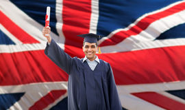 Happy male student with diploma over british flag. Education, graduation and people concept - happy male student in mortarboard and bachelor gown with diploma Royalty Free Stock Photos