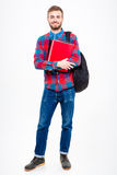 Happy male student holding books. Full length portrait of a happy male student holding books standing isolated on a white background Royalty Free Stock Photo
