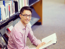 Happy male student holding books at the library Stock Images