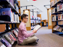 Happy male student holding books at the library Stock Image