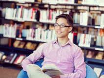 Happy male student holding books at the library. Happy male asian student holding books at the library Stock Photos