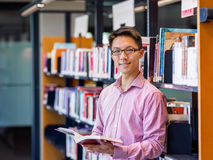 Happy male student holding books at the library. Happy male asian student holding books at the library Royalty Free Stock Photography