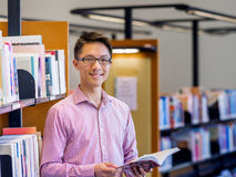 Happy male student holding books at the library Stock Photos