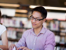 Happy male student holding books at the library. Happy male asian student holding books at the library Stock Photo